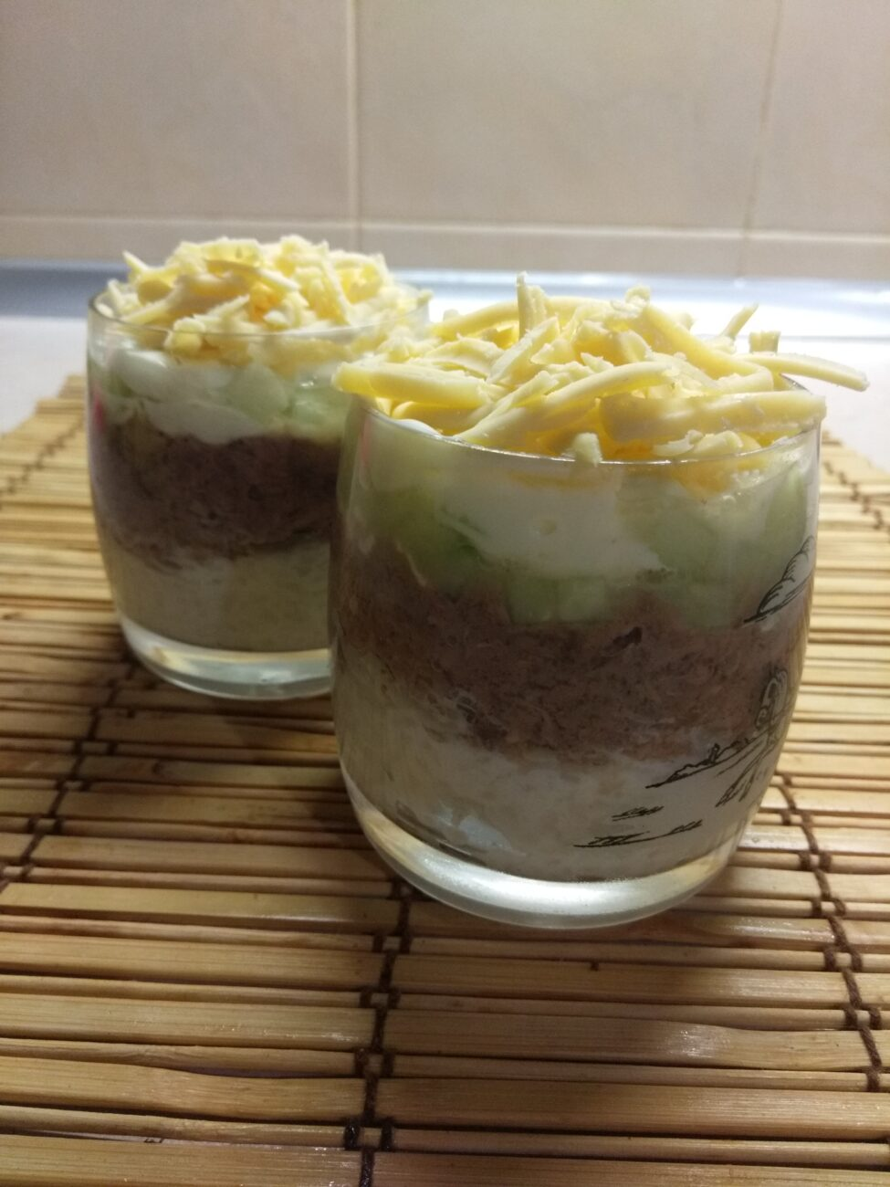 Слоёный салат из тунца, риса, огурцов и сыра